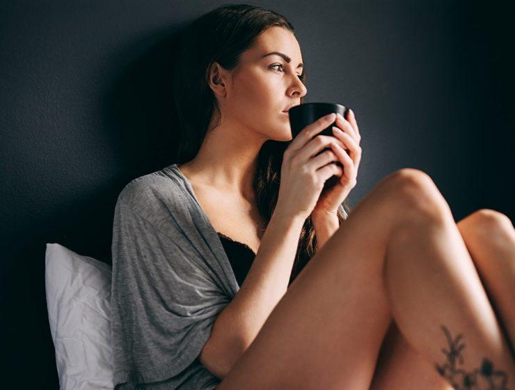 Femeie singura care bea cafeaua in pat
