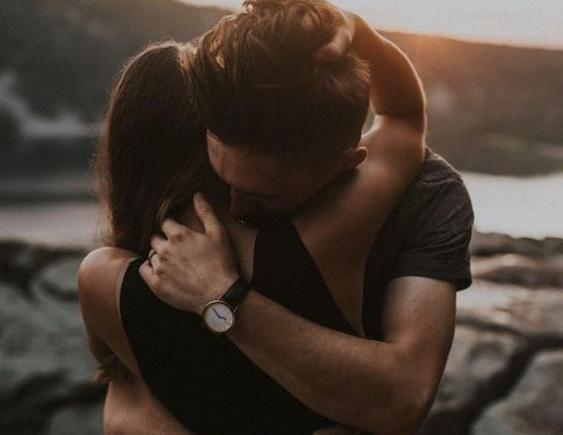 Barbat imbratisand strans in brate o femeie