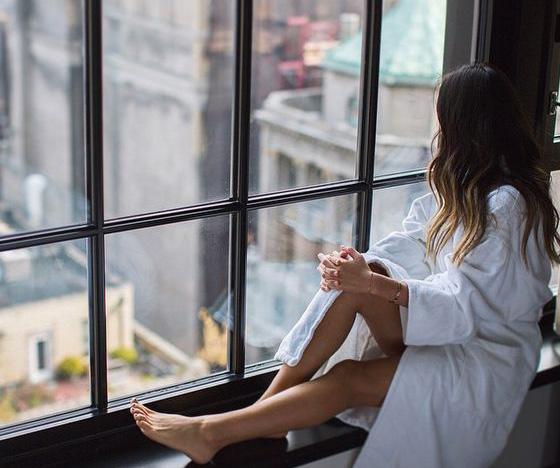 Femeie singura stand la geam