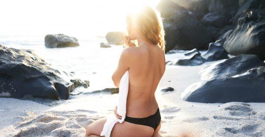 femeie stand pe plaja in soare